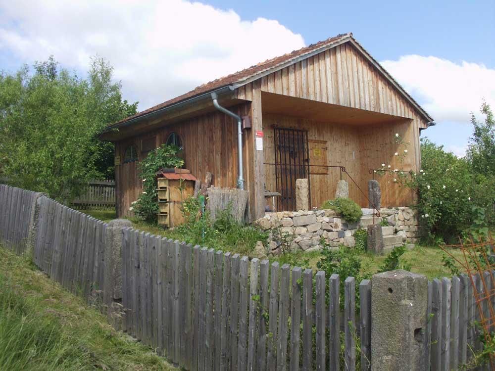Das Bienen- und Gerätehaus, im Jahr 2010 zu großen Teilen aus recycelten Baumaterialien errichtet. (Foto: Juni 2014)